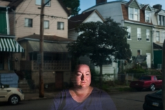 Jackie Stock, 33, sits for a portrait in her living room as her street is reflected in her screen door on Wednesday, July 11, 2018, at her Hazelwood home. Stock, a housekeeper at Mercy's environmental services, says she doesn't have enough money once she pays for food, rent, bills, and transportation to afford a rent increase if Amazon's new HQ2 were to drive up rental prices in the neighborhood. (Stephanie Strasburg/Post-Gazette) Heinzelwood0722